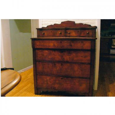 Restored flame mahogany veneered finish on an anitque dresser.